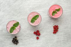 Fresh milk, currant, raspberry and red currant. Drinks on wodeen table, assorted protein cocktails with fresh fruits Stock Photography