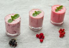 Fresh milk, currant, raspberry and red currant. Drinks on wodeen table, assorted protein cocktails with fresh fruits Royalty Free Stock Image