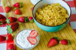Fresh milk in glass bottle, cereals in green blue ceramic bowl, tasty yogurt in small glass bowl with a lot of strawberries around stock image