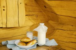 Fresh milk in a glass bottle and a glass, next to the pies on a wooden table. The concept of healthy organic products. Rusty style royalty free stock photography