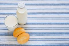 Fresh milk in a glass bottle and glass, on a striped towel, next to freshly baked bakery products. The concept of organic food stock image