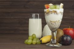 Fresh milk in the glass and muesli breakfast on a wooden table. Oatmeal with milk and curd, meals for athletes. Stock Photos