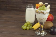Fresh milk in the glass and muesli breakfast on a wooden table. Oatmeal with milk and curd, meals for athletes. Royalty Free Stock Photography