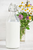 Fresh milk in old fashioned bottle and wildflowers Stock Photography