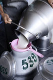 Fresh milk. Worker pouring milk into a container Royalty Free Stock Images