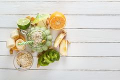 Fresh milkshake of tropical fruits, lemon and mint along with oat flakes. Top view. Useful food. Copy space Stock Images