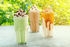 Fresh milkshakes on a table. Fresh milkshakes on a terrace table. Mint, chocolate and salted caramel flavors. Tasty and good for health royalty free stock image