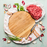 Fresh minced meat with fresh herbs and spices around wooden cutting board. On light blue background, top view, copy space Stock Photo