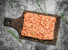 Fresh minced meat on an old wooden board. On a rustic background Royalty Free Stock Photo