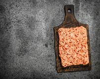Fresh minced meat on an old wooden board. On a rustic background Stock Photography