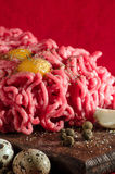 Fresh minced meat, quail eggs and spices. On the kitchen Board on a red background Stock Photography