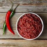 Fresh minced meat in a white bowl on a wooden table, top view. Authentic cuisine Stock Image