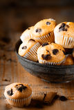 Fresh mini muffins on aged wood background