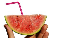 Fresh mini watermelon Citrullus Lanatus var. Lanatus slice with plastic violet straw and drops of water held in left hand on white Royalty Free Stock Image