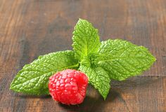 Fresh mint leaves and raspberry. On wooden background Royalty Free Stock Image