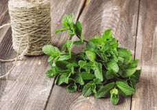 Fresh mint on the old wooden table. Bunch of fresh mint on the old wooden table with twine Royalty Free Stock Photo