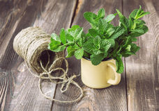 Fresh mint on the old wooden table. Bunch of fresh mint in yellow mug on the old wooden table with twine Royalty Free Stock Photos