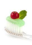 Fresh Minty Toothbrush. Fresh minty toothpaste on a clear toothbrush with a green mint leaf and red cranberry on white Stock Photos