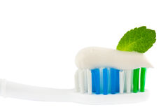 Fresh Minty Toothbrush. Closeup of the head of a toothbrush with fresh white toothpaste and a green mint leaf, conceptual of oral freshness Stock Photo