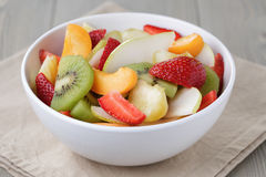 Fresh mix fruit salad with strawberry, kiwi and peach. On wood table stock photo