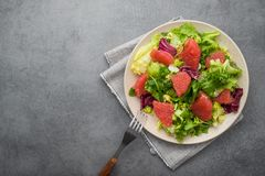 Fresh mix salad with lettuce, green arugula and sliced grapefruit in a plate. Diet food background. Top view stock photography