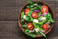Fresh mixd salad with rucola, tomatoes cherry, feta cheese and red onion in a bowl on rustic wooden table. top view stock photos