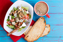Fresh mixed feta salad and coffee on picnic table. Fresh mixed feta salad on a platter served with frothy espresso coffee and toasted baguette on a colorful Royalty Free Stock Photos