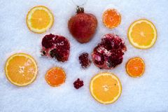 Fresh mixed fruit on snow. Fresh mixed fruit with orange, pomegranate, mandarin on snow Royalty Free Stock Photography