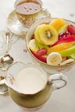 Fresh Mixed Fruit Salad and Cream in Old Crockery. Fresh fruit salad served in an old fashioned bowl, with cream and a cup of tea. Contains red and green apple Stock Images