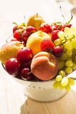 Fresh mixed fruits, berries in colander. Love fruit, berry. Sunlight Royalty Free Stock Image