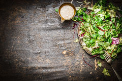 Fresh mixed green salad with oil dressing rustic wooden background, top view. Healthy food Stock Photography