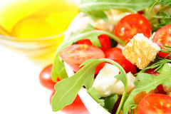 Fresh mixed salad. Mixed salad with cherry tomatoes, arugula, mozzarella and olive oil on white background Stock Image