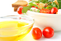 Fresh mixed salad. Mixed salad with cherry tomatoes, arugula, mozzarella and olive oil on white background Royalty Free Stock Photos