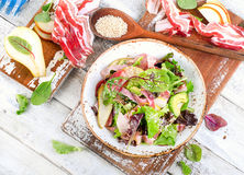 Fresh mixed salad with bacon on a white wooden table. royalty free stock photos