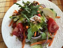Fresh mixed salad with green stuff, nuts and fruits Royalty Free Stock Photo