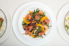 Fresh mixed salad with nuts, shrimps, salmon and Royalty Free Stock Images