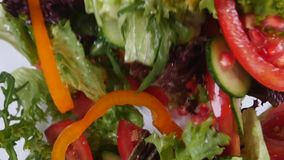 Fresh mixed vegetables falling into bowl of salad stock video footage