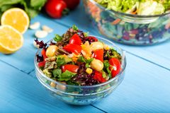 Fresh mixed vegetables salad in a bowl. On wooden background royalty free stock photo