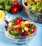 Fresh mixed vegetables salad in a bowl. On wooden background stock images