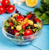 Fresh mixed vegetables salad in a bowl. On wooden background stock photography
