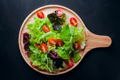Fresh mixed vegetables salad. On a wooden plate royalty free stock image