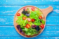 Fresh mixed vegetables salad. On a wooden plate stock images