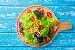 Fresh mixed vegetables salad. On a wooden plate stock image