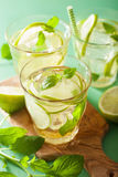 Fresh mojito cocktail and ingredients over green background.  Stock Photo
