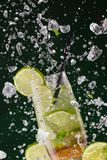 Fresh mojito drink with ice cubes and splashes Stock Photos
