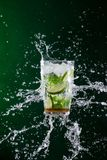 Fresh mojito drink with liquid splash and crushed ice in freeze motion. royalty free stock photos