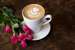 Hot cappuccino with foam in the form of a heart stands on a dark wooden background beside lies a twig of roses. place. A fresh morning cappuccino in a white cup Stock Photo