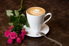 Hot, fragrant coffee stands on a wooden texture table next to a rose. A fresh morning cappuccino in a white cup with a heart of foam, stands on a wooden table Stock Photos