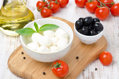 Fresh mozzarella in a bowl, olives and cherry tomatoes Royalty Free Stock Images