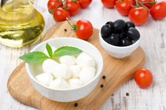 Fresh mozzarella in a bowl, olives and cherry tomatoes Stock Images